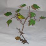 Hooded warbler on branch.